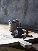 Chunks of chocolate and knife on wooden chopping board