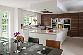 Island counter and dark wooden cupboards in modern kitchen-dining room