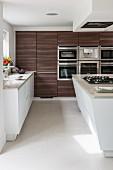 Moderne Wohnküche mit Kochinsel und dunklen Holzfronten