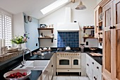 Country-house kitchen with black worksurface and vintage-style gas cooker