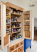 Stripped wooden cupboard with multiple spice racks on inside of doors