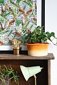 Still-life arrangement of ivy next to gold cactus ornament in front of artwork with monkey motif