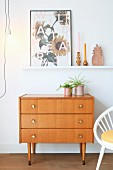 Houseplants in pink pots on 60s chest of drawers below floral picture on white, wall-mounted shelf