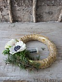 Straw wreath being decorated with anemones and larch twigs