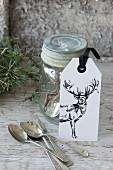 Etikett mit einem Hirsch lehnt am Einmachglas mit Silberbesteck