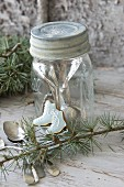 Ice-skate-shaped iced biscuit leaning against screw-top jar with silver cutlery inside