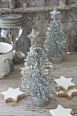 Arrangement of cinnamon stars and silver Christmas-tree ornaments