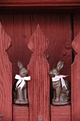 Two chocolate bunnies with pink ribbons on red picket fence