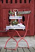 Etagere mit österlicher Blumendeko auf rotem Gartenstuhl