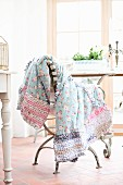 Floral blanket with crocheted edge draped over chair