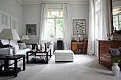 Salon mit weißem Polstermöbel, dunklem Couchtisch und antiker Kommode