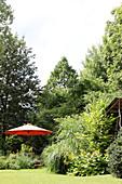 Blick auf Rasenfläche, Staudenbeet und Sonnenschirm im Garten