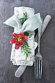 Linen napkin tied with rosemary sprig and flower next to vintage cutlery