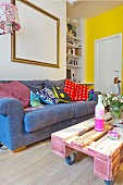 Comfortable sofa with various scatter cushions and pallet coffee table