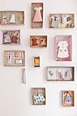 Miniatur-Kleidungsstücke und feminine Accessoires in einzelnen, gemusterten Pappschachteln