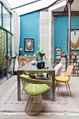Dining table and various chairs in front of blue wall and below glass extension ceiling