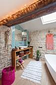 Bad mit Sichtmauerwerk und Waschtisch aus Holz vor blauen Fliesen