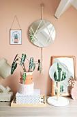 Wandspiegel mit Makramee und Holzperlen an apricotfarbener Wand, davor Zimmerpflanzen