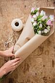Frauenhände wickeln rosafarbenen Blumenstrauß in Packpapier