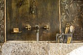 Vintage stone sink with brass wall-mounted taps in vintage surroundings