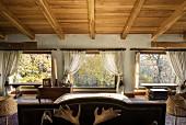 Dachgeschossschlafzimmer im Landhausstil mit Fensterfront und Waldblick