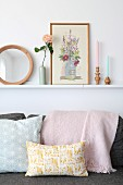 Ornaments on narrow shelf above pastel cushions on sofa