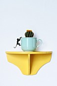 Cactus planted in cup on yellow wall bracket