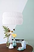 Origami pendant lamp above retro accessories on round table