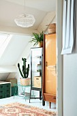 Various retro furnishings and house plants below sloping ceiling
