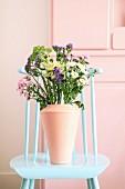 Strauß mit verschiedenfarbigen Chrysanthemen auf einem Stuhl