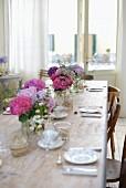 Several vases of hydrangeas on set table