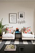 Two white armchairs with colourful floral scatter cushions against wall