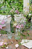 Vases of wildflowers on worn table below window