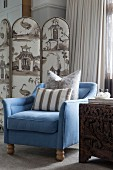Blue armchair with beige scatter cushions in front of upholstered screen
