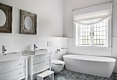 Free-standing bathtub and two old chests of drawers converted into washstands