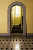 View through archway into stairwell with yellow walls