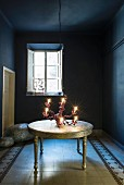 Chandelier on table in blue room with patterned floor