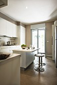 Island counter and bar stools in white, contemporary fitted kitchen