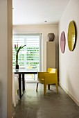 View into dining area with yellow designer chair