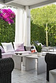 Roofed terrace in front of flowering bougainvillea climbing over hedge