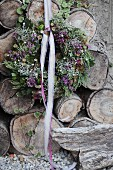 Autumnal wreath with lace ribbon on stack of weathered firewood