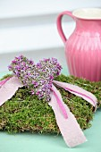 Pink ribbon and heather love-heart on romantic moss cushion