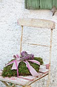 Romantic cushion of moss on vintage wooden chair against house façade