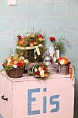 Flowers arranged in kitchen utensils on top of old ice-cream cart