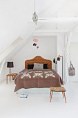 Double bed with headboard in renovated attic apartment
