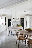 Island counter and dining table in large kitchen with concrete floor