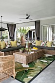 Rattan furniture on veranda with jungle-patterned rug