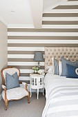 Gestreifte Wand im eleganten Schlafzimmer in Beige, Weiß und Blau