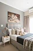 Child's bedroom in natural shades with picture of wolf above bed