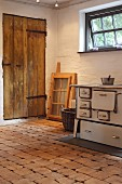 Old, wood-burning kitchen stove on rustic floor made of wooden tiles